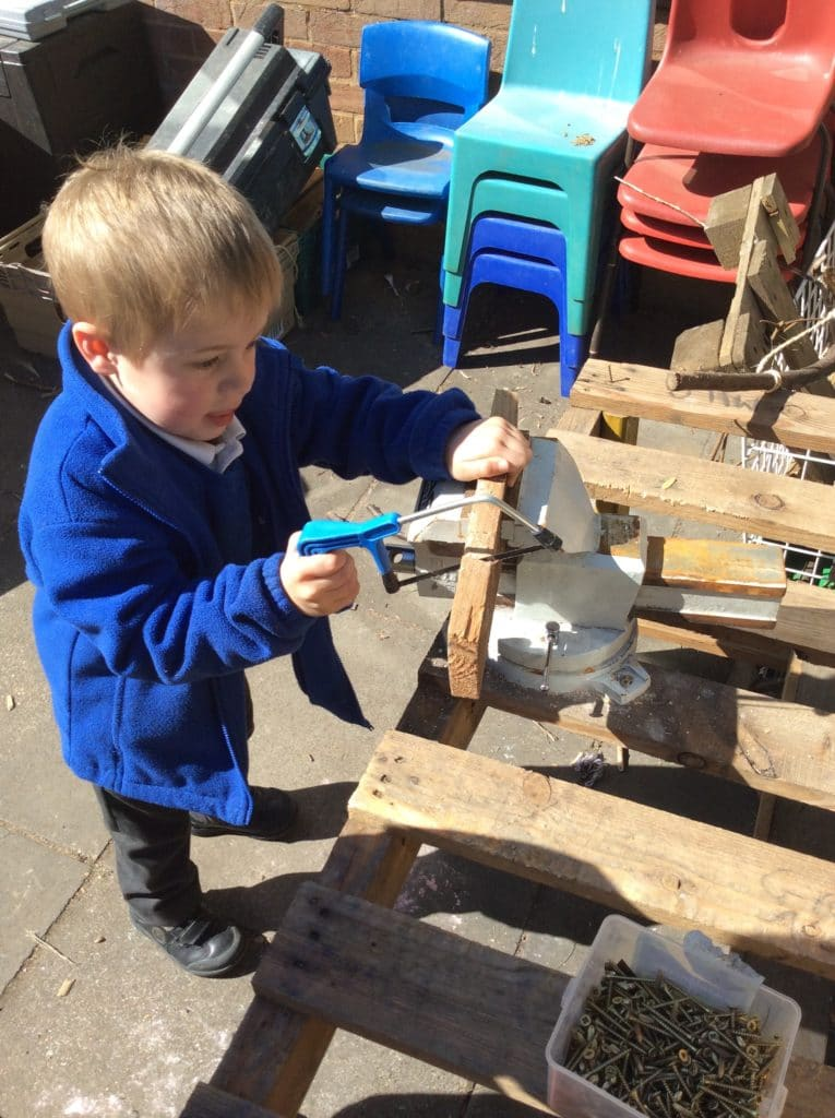 picture of boy sawing a piece of wood